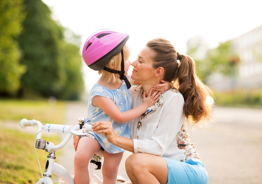 Eskimo kisses between a proud mother and daughter who has just learned how to ride her bicycle. The mother kneels lovingly next to her daughter holding her gently. The pink helmet evokes bicycle safety. A warm summer's evening in a city park.