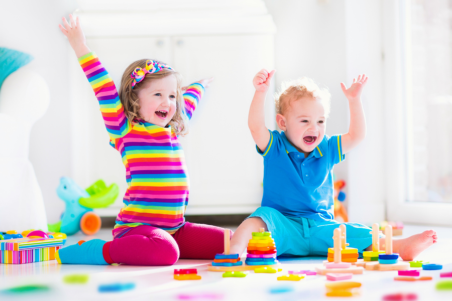 Kids playing with wooden toys. Two children cute toddler girl and funny baby boy playing with wooden toy blocks building towers at home or day care. Educational child toys for preschool and kindergarten. ** Note: Soft Focus at 100%, best at smaller sizes