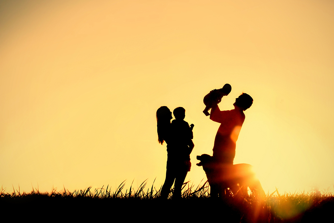A silhouette of a happy family of four people mother father baby and child and their dog in front of a sunsetting sky with room for copy space or text